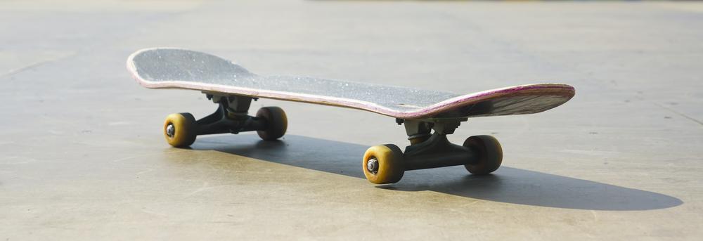 Skateboard Stand on Wooden floor against skate park background.